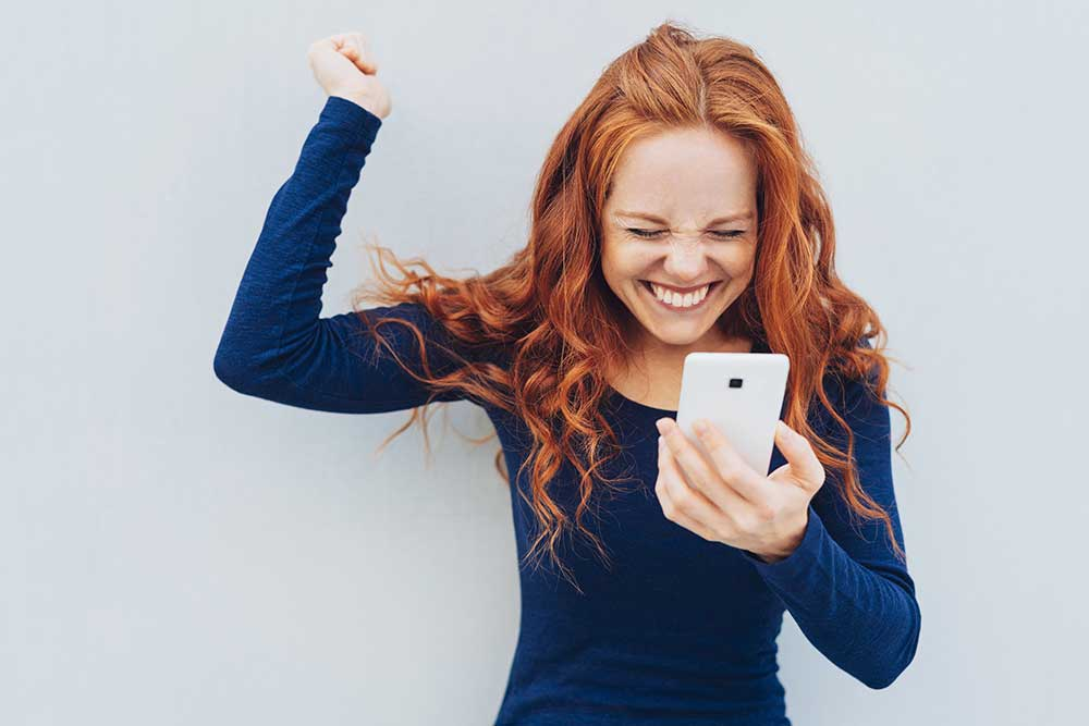 Excited woman with cell phone